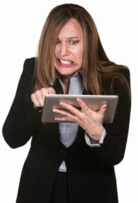 woman looking at a ipad with grimace on face